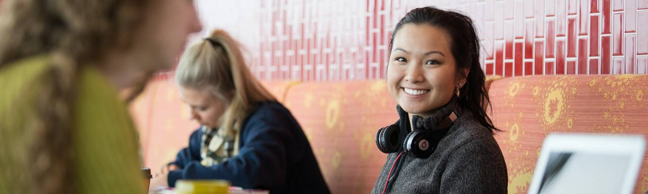 Photo of a female student smiling at the camera with headphones around her neck.